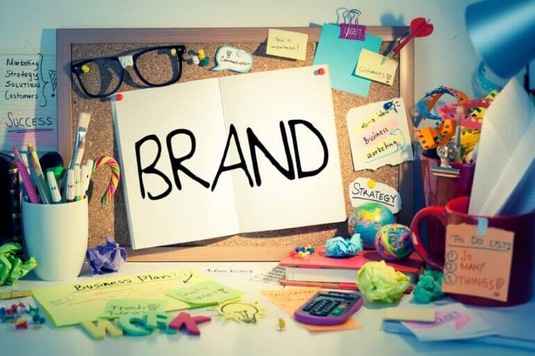 """brand"" written on A4 white paper pinned on corkboard"
