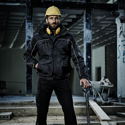 ppe workwear: man in safety jacket and hat standing in derelict building