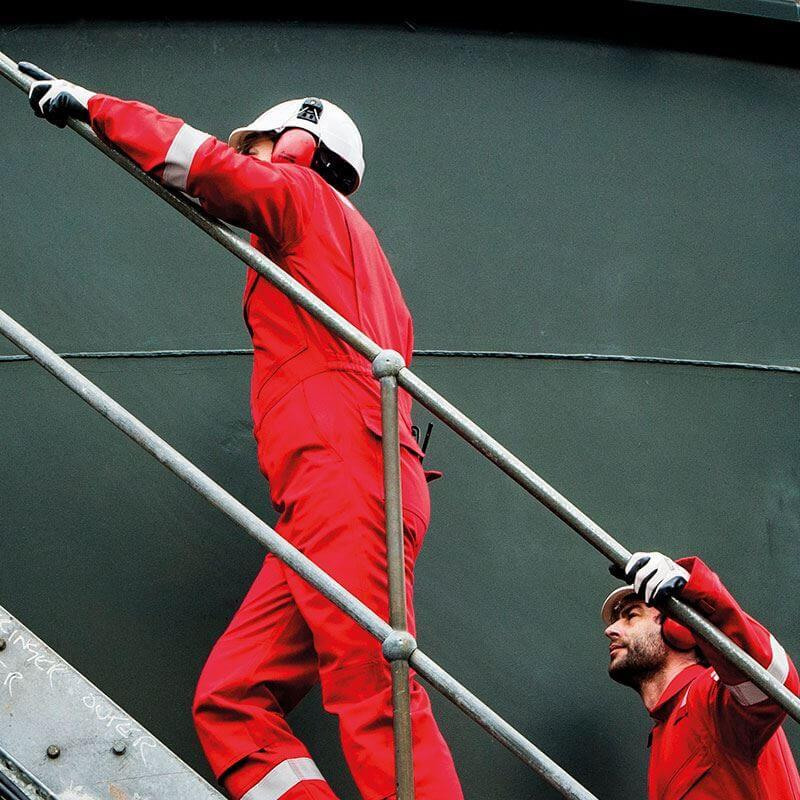 ppe workwear - men climbing stairs wearing protective overalls, hard hats and ear protection